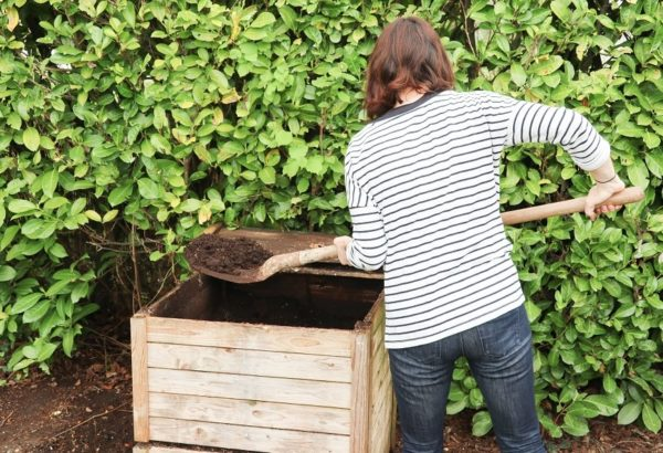 woman with shovel at outside compost bin