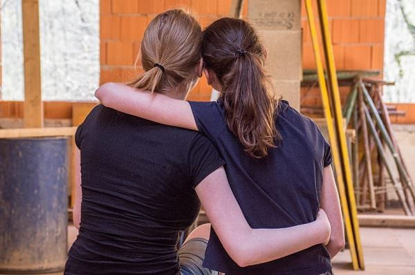 two women sitting on a bench and hugging