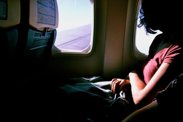 woman passenger looking out airplane window