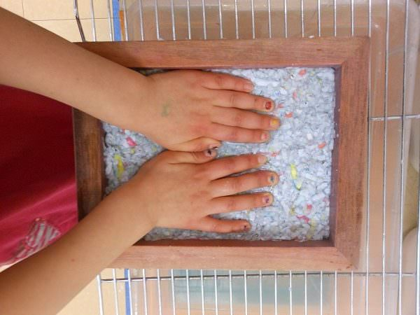 Childs hands making homemade paper for earth day