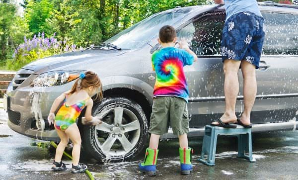 Brother and sister help dad wash a car in the driveway