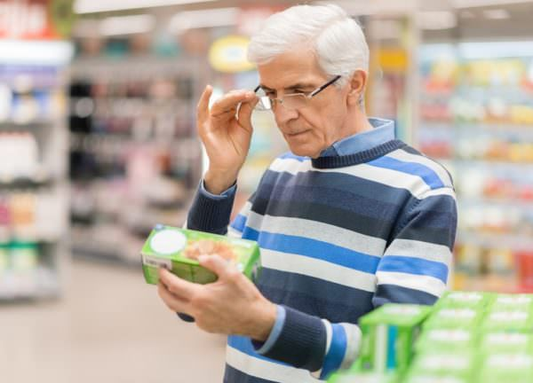 white-haired man reading food label in grocery store