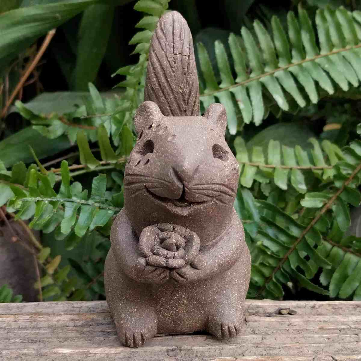 ceramic-chipmunk-holding-flower-tail-up-outdoor-sculpture-by-margaret-hudson-earth-arts-studio-1