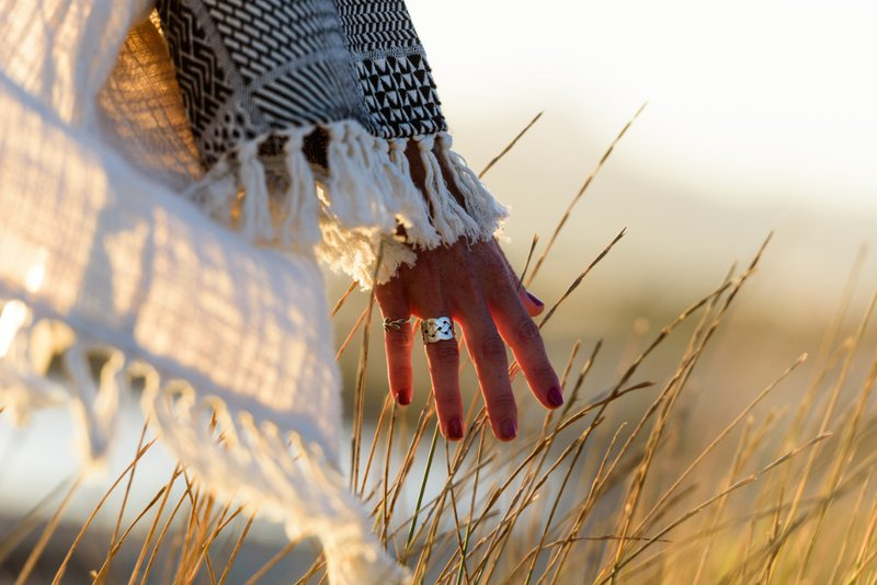 woman feels tall grasses with her hand