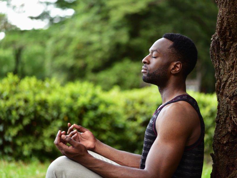 Reflection - Man Meditates Sitting At Base of Tree