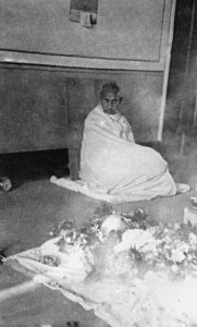 Picture of Gandhi sitting in a corner of a room, wrapped in a shawl, looking at Ba's body lying on a mat in the foreground.