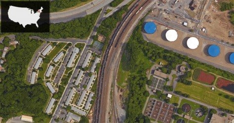 Ezra Prentice Homes is the complex of grey-roofed buildings bordering the left side of the train tracks—where a line of tanker cars can be seen lined up. Global's facility and storage tanks are on the opposite side of the rail tracks.