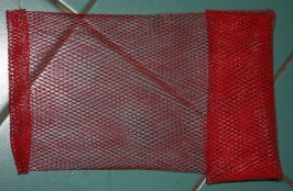 First we folded and tacked up one end of the bag with a waterproof, nylon thread.