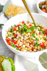 corn salsa in a white bowl on a marble board