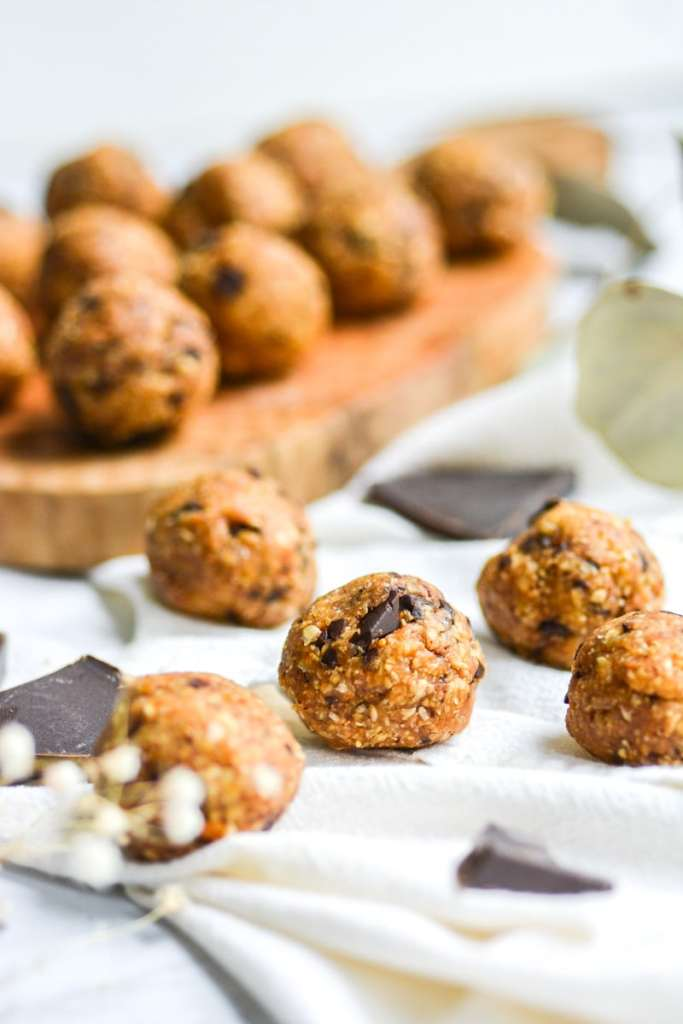 portrait of vegan cookie dough bliss balls on a white board with chocolate pieces