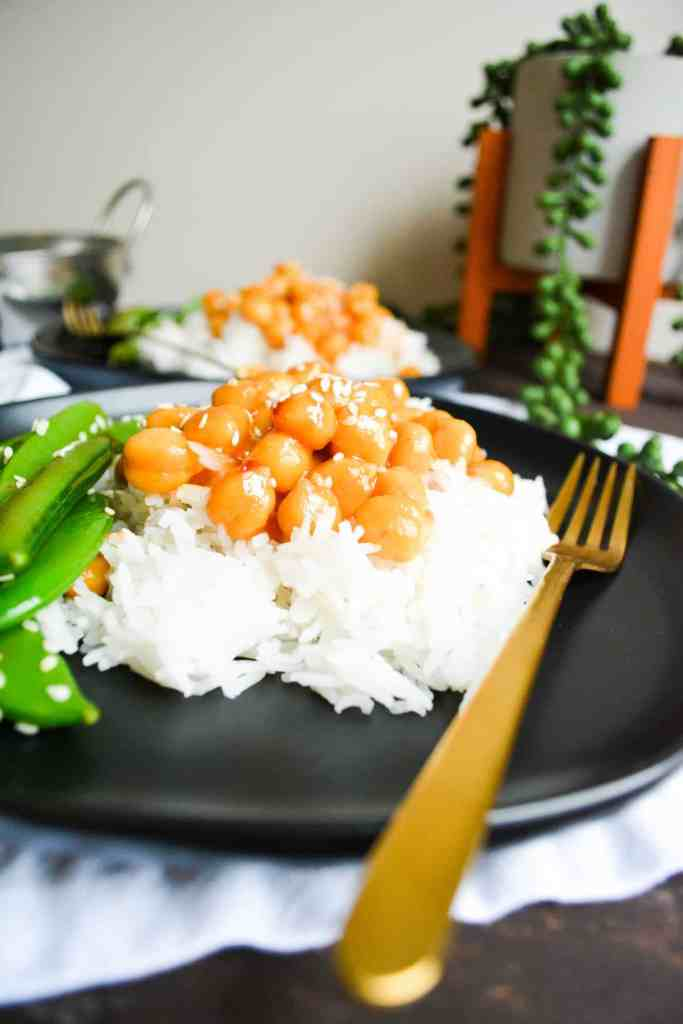 Close up of sticky, sweet + spicy chickpeas over rice