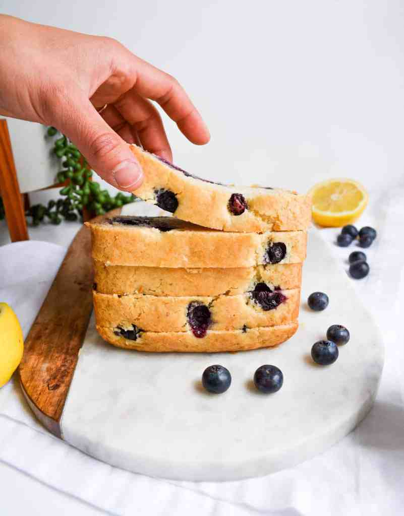 Hand Picking up a slice of stacked One-Bowl Blueberry Lemon Loaf slices