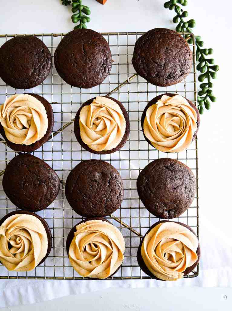 Rosettes of vegan peanut butter frosting on chocolate cookies