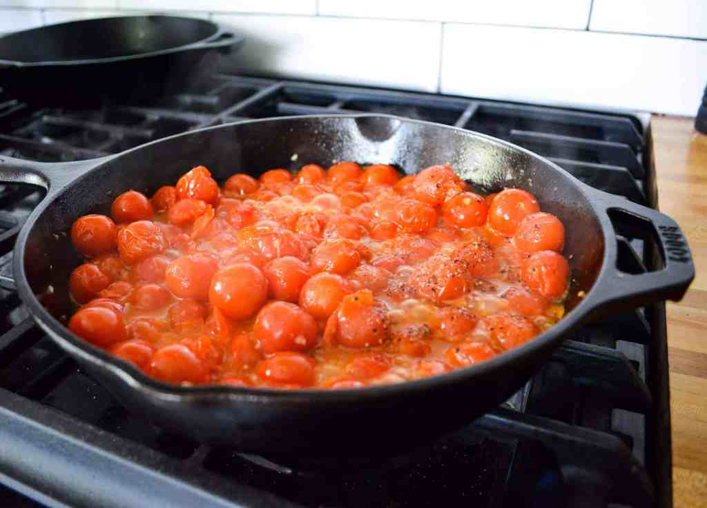 Cherry tomatoes cooking in a cast iron pan