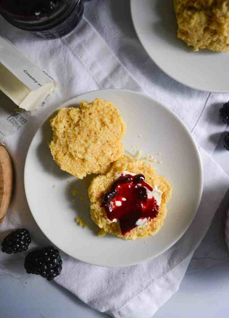 Fluffy Cornmeal Drop Biscuit on a white plate with blackberry jam