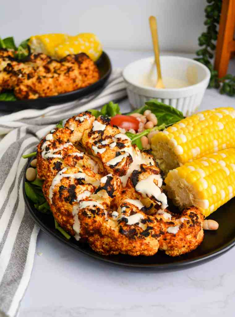 portraid of two black plates with cauliflower steaks and corn