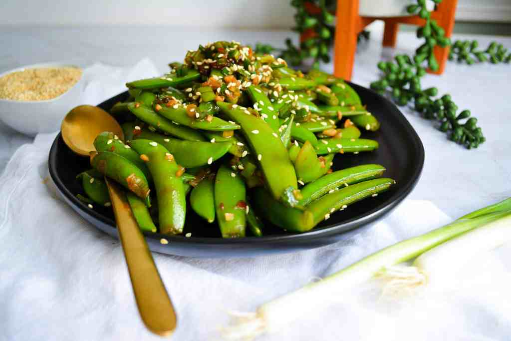 Landscape of snap peas on black plate with gold spoon