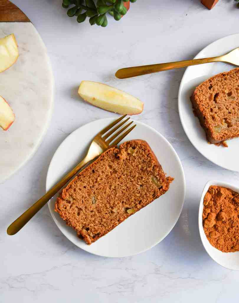 Portrait of Easy Chai Spiced Apple Loaf on a white plate with a gold fork