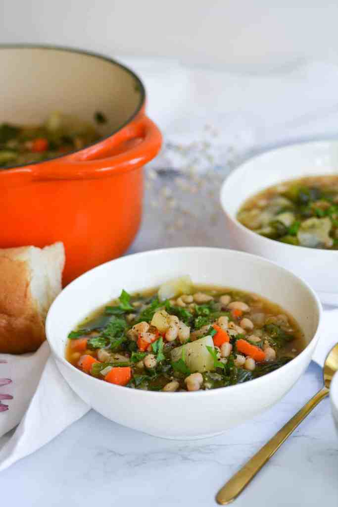 Two bowls of soup with bread and an orange dutch oven in the background