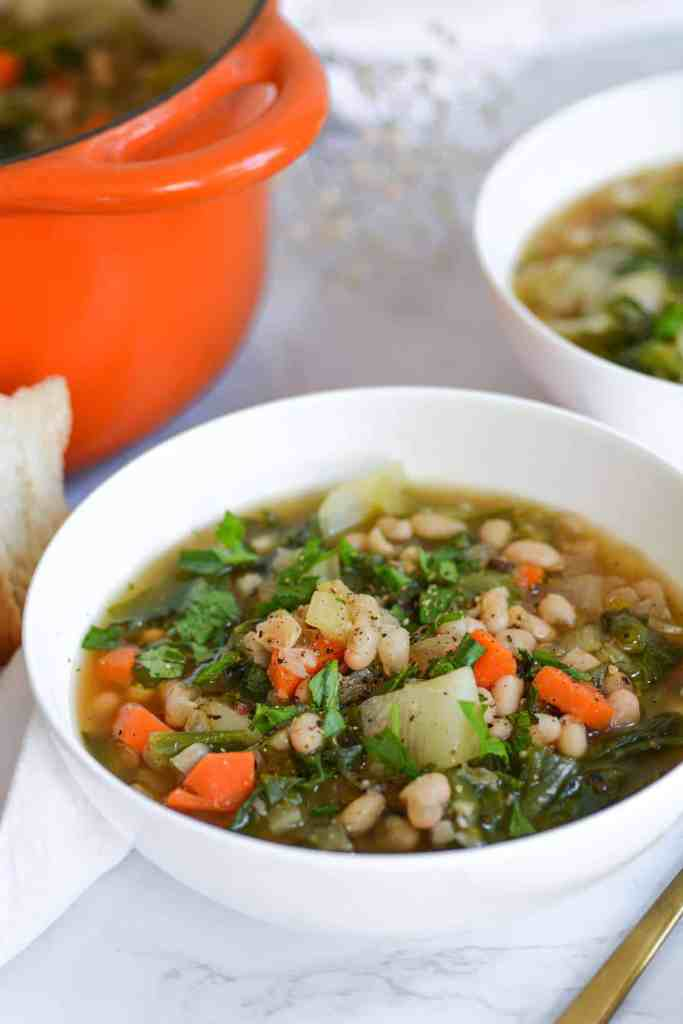 Close-up of a bowl of Italian White Bean and escarole soup with an orange dutch oven in the background