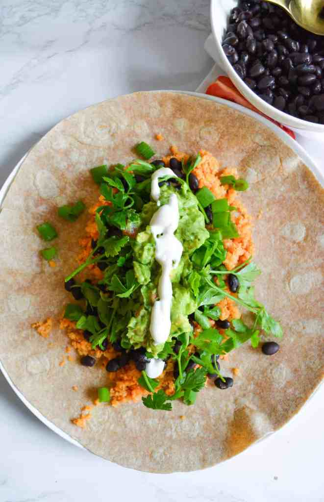 A burrito with buffalo cauliflower rice, black beans, guac and ranch dressing that hasn't been rolled up yet