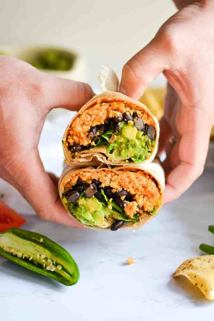 2 hands holding 2 halves of buffalo cauliflower rice burritos with ranch and guac