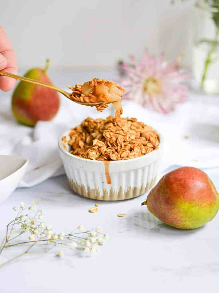 Spoon with a bite of Healthy Pear Crisp on it with a white ramekin and small pears in the background