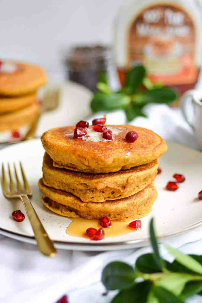 stack of 3 whole grain pumpkin spice pancakes with vegan butter, maple syrup and pomegranate seeds