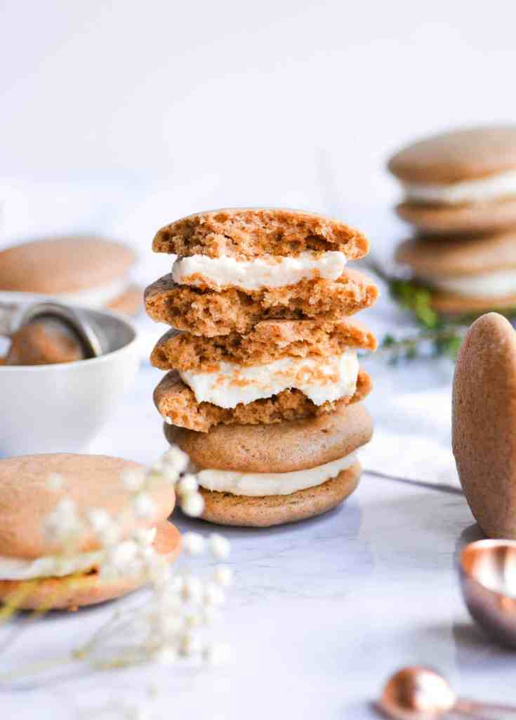 Portrait up stacked Chai Spiced whoopie pies with the top one cut in half on a white background