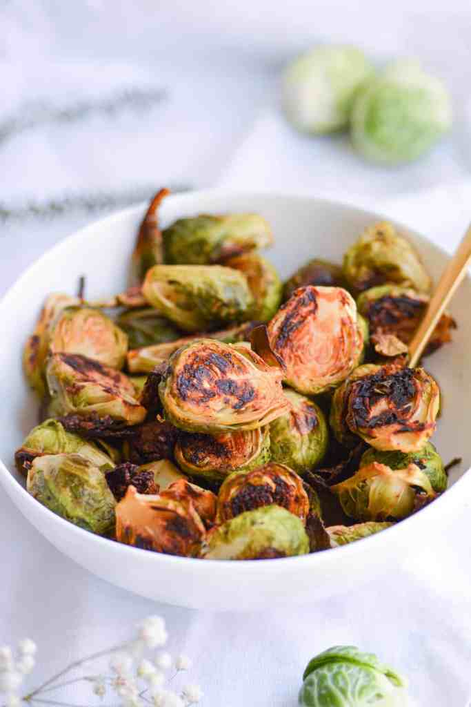 Roasted Maple Dijon Brussels Sprouts in a white bowl with a gold spoon