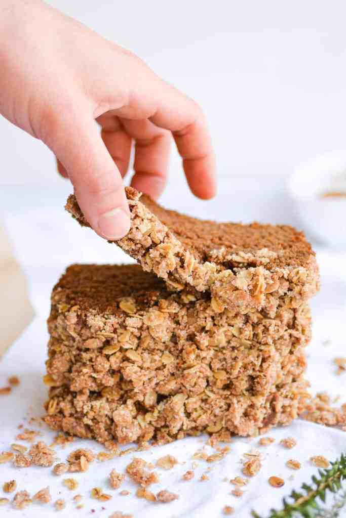 Hand picking up a piece of gingerbread coffee cake from a stack of slices