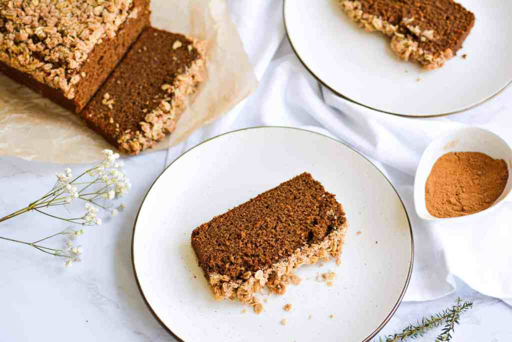 Overhead of 2 plates with gingerbread coffee cake loaf slices with the rest of the loaf in the background