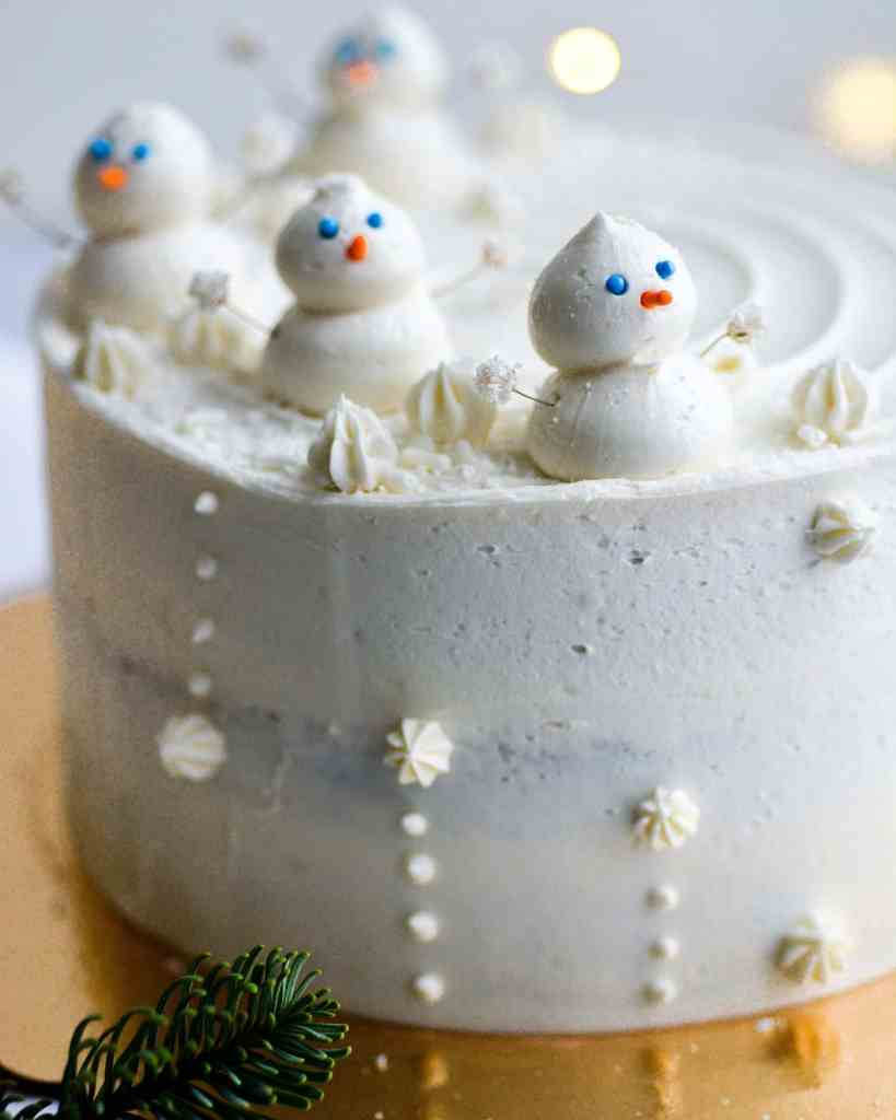 Vegan Gingerbread Cake frosted with vanilla buttercream and topped with buttercream snowmen