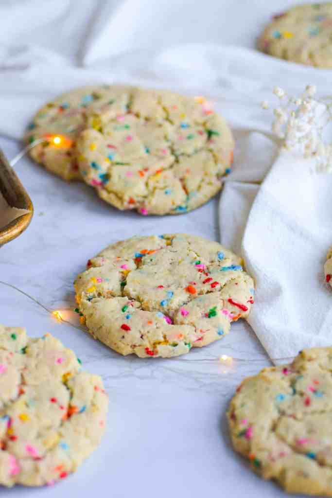 Funfetti Sugar Cookies laid out on a marble board with a white tea towel