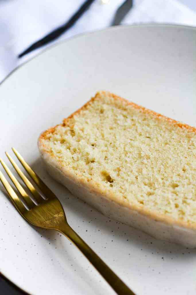 Close up of a slice of pound cake on a tan plate next to a gold fork