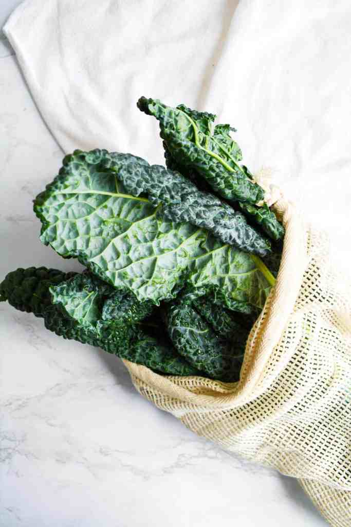 Tuscan Kale in a reusable produce bag on a marble board
