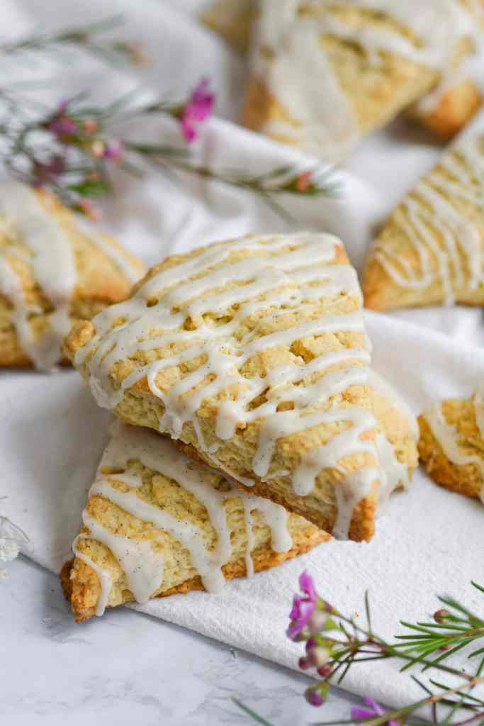 two vanilla bean scones stacked with more scones in the background