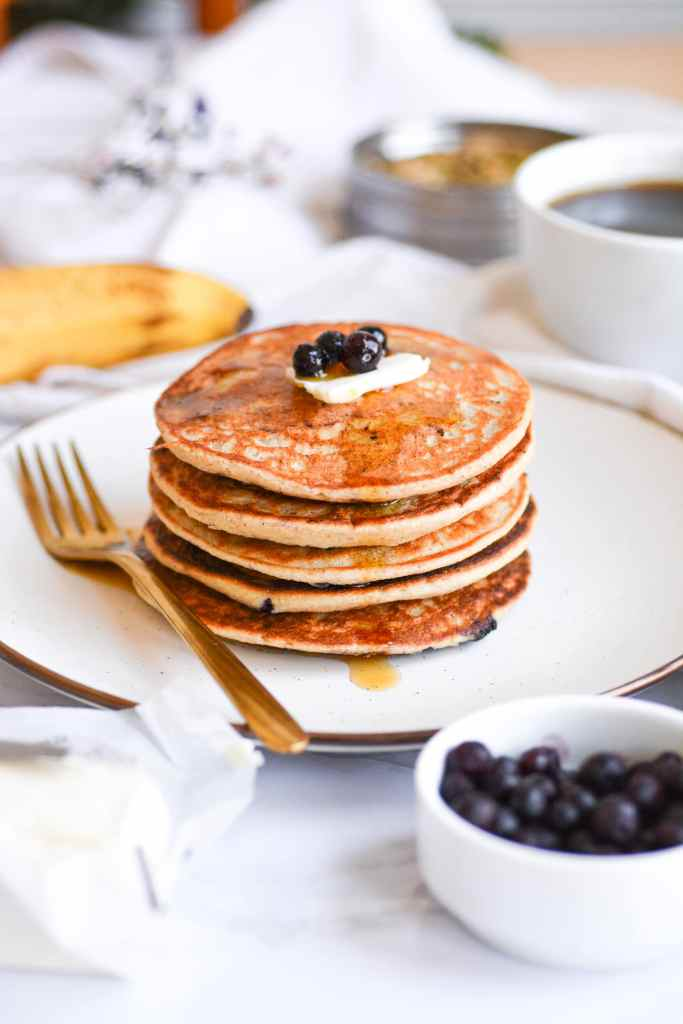 Blueberry Cardamom blender pancakes stacked on a tan plate topped with vegan butter. blueberries and maple syrup