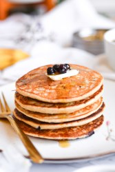 Close up of blueberry cardamom blender pancakes topped with vegan butter and blueberries