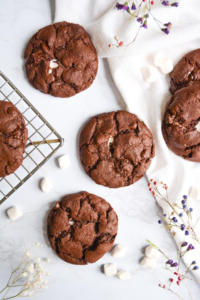 Overhead shot of marshmallow stuffed double chocolate cookies on a white board with a white tea towel and a wire cooling rack