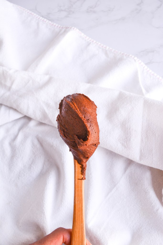 Thickened Chocolate Ganache on a spatula against a white background