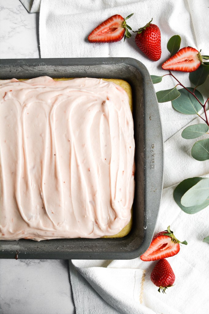 Vegan Lemon Cake with in a 9x13 pan on a white marble board with greenery and strawberries