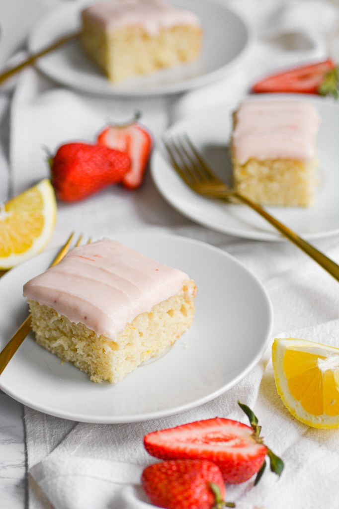 Portrait of 3 Pieces of Vegan Lemon cake on white plates with lemon wedges and strawberries