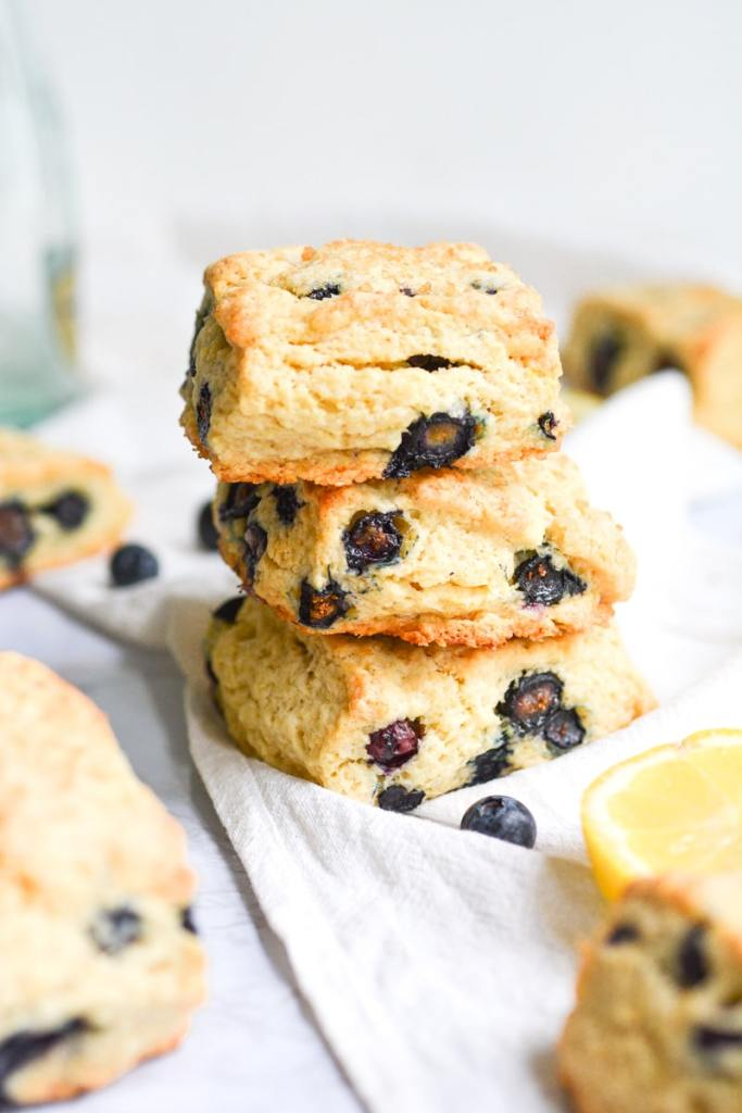 Three Vegan blueberry scones stacked on a white board