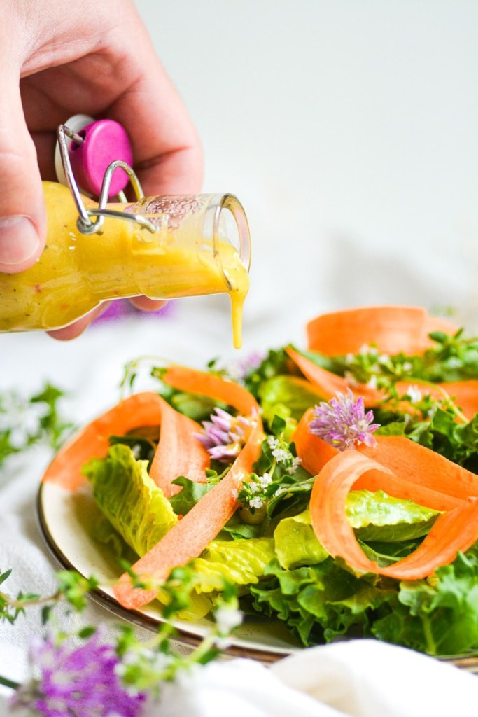 Hand holding a jar pouring honey mustard dressing onto salad