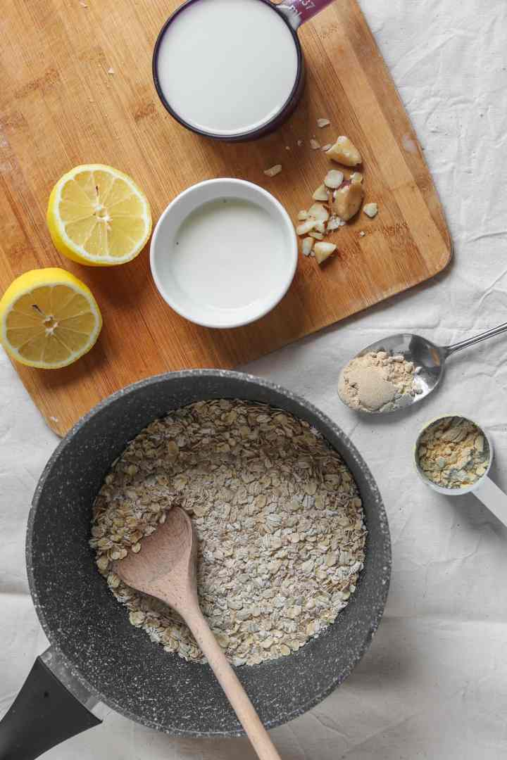 Oatmeal ingredients on a table, including oats, milk, soy yoghurt, maca powder, protein powder, brazil nuts and lemon