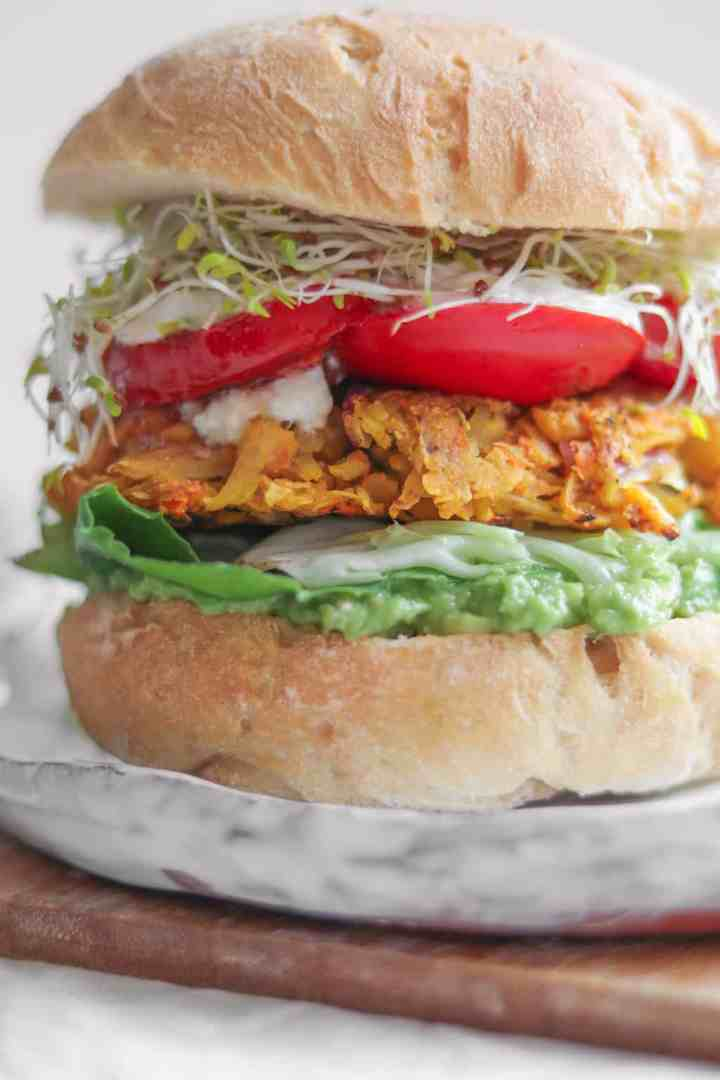 Closeup of Vegan chickpea fritter sandwich with avocado, mixed greens, tomatoes, soy yoghurt and alfalfa sprouts