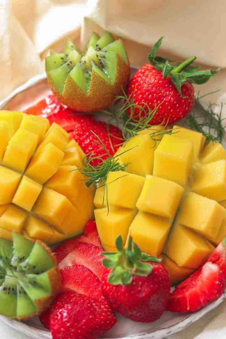 Fruit platter for breakfast with mango, strawberries and kiwi