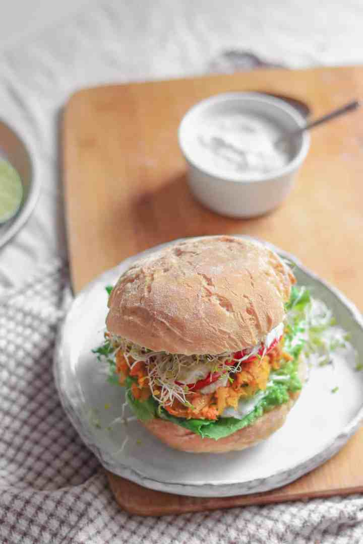 Vegan fritter sandwich with avocado, mixed greens, alfalfa sprouts, panfried tomatoes, soy yoghurt and alfalfa sprouts resting on a table