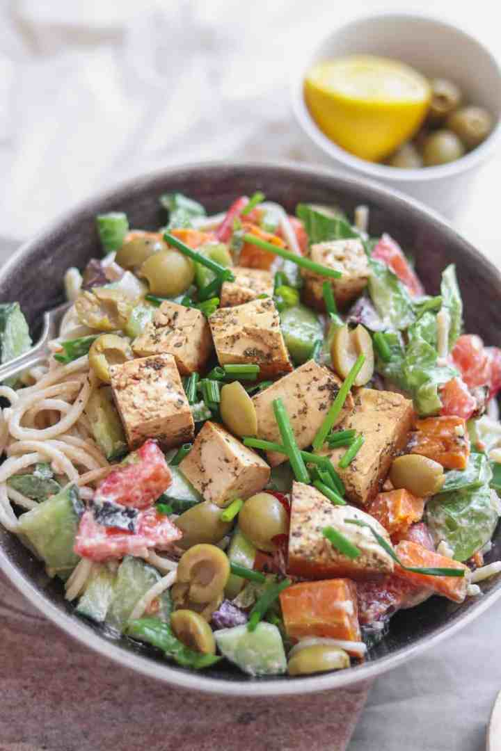 Vegan cold pasta salad with vegetables, tofu, green olives and a tahini dressing in a large mixing bowl, with lemon and more olives in the background